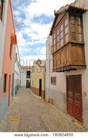 AGULO, LA GOMERA, SPAIN: Cobbled street with colorful facades and a wooden balcony
