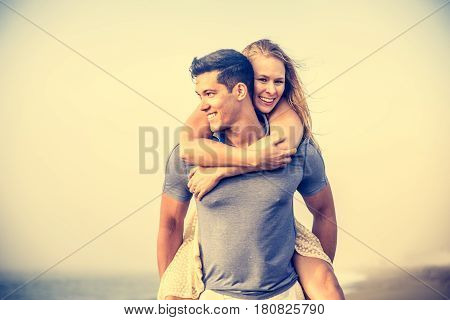 Couple share romantic moments on the beach during a foggy day - Romantic date beautiful young couple cuddling and kissing
