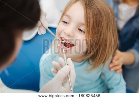 Not scary at all. Adorable entrusted brave kid being unafraid of the dentist while paying him regular visit for running a checkup