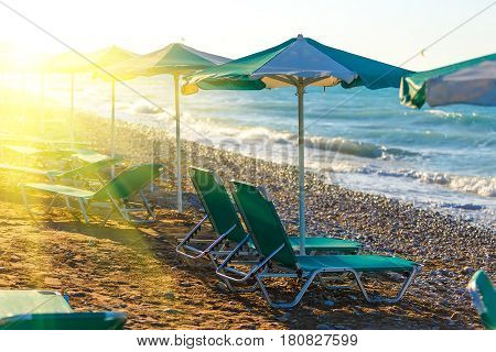 Pair of sun loungers and a beach umbrella on a beach perfect vacation concept