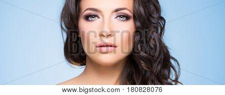 Portrait of beautiful brunette over blue background. Beauty concept.