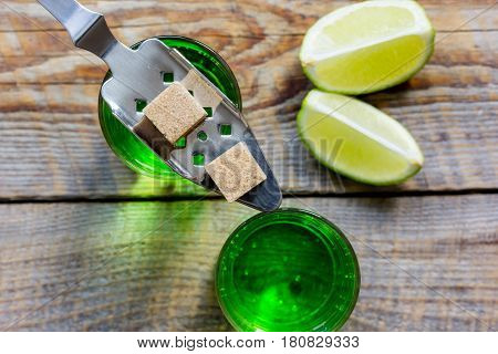 green absinthe in glass with fresh lime slices on wooden table background top view