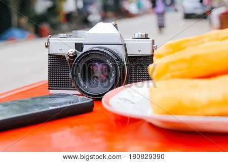 Old Vintage Analogue Camera on the Table with Phone and Youtiao