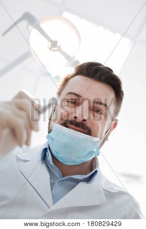 No chance for being scared. Emotional friendly distinguished specialist using a dental drill while running some manipulations for treating teeth of his patient