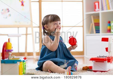 Pretty child girl playing with a toy kitchen in children room or kindergarten