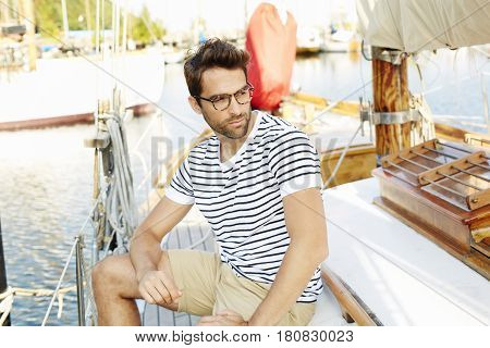 Serious boat man sitting on boat in habour looking away