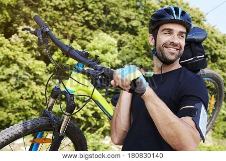 Strong Handsome Man carrying bicycle in woods  smiling