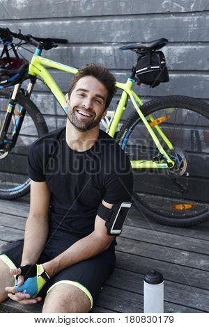 Laughing cyclist sitting relaxing by bicycle portrait