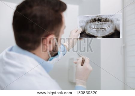 Looking at the details. Best private pediatric doctor looking at the scan of clients teeth and working on diagnosis before starting any procedures