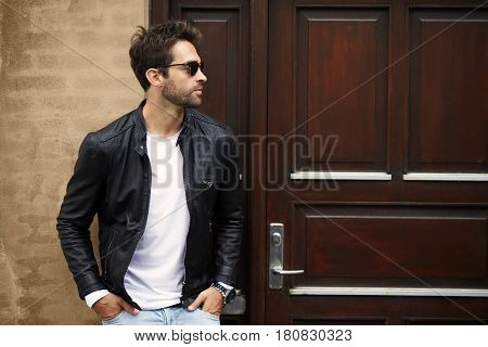 Handsome Leather dude in sunglasses looking away