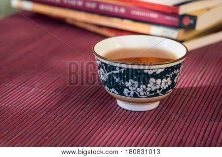 Closeup of a cup of tea and books in an outdoor shaded light ambiance