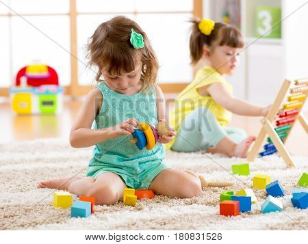 Children preschooler girls play logical toy learning shapes arithmetic and colors at home or nursery