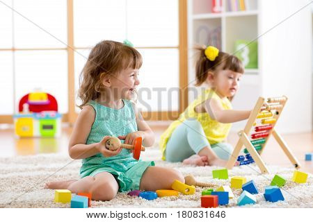 Little kids girls playing with abacus and constructor toys in kindergarten playschool or daycare center