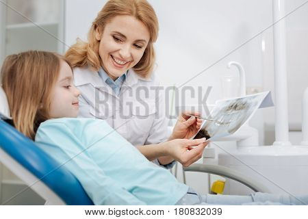 You made a great job. Skillful experienced pediatric dentist showing her little patient xray of her teeth and explaining how much her dental health improving