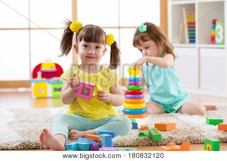Kids playing with blocks together. Educational toys for preschool and kindergarten child. Little toddlers girls build toys at home or daycare.