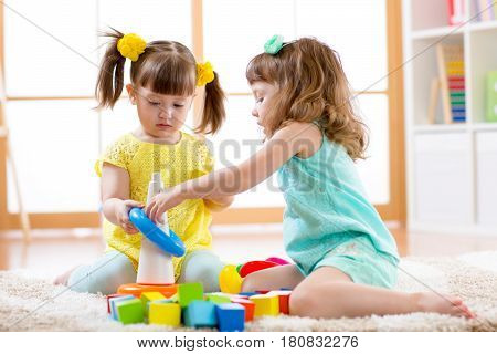 Children playing together. Toddler kid and baby play with blocks. Educational toys for preschool and kindergarten child. Little girls building pyramid toys at home or daycare.