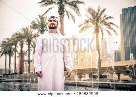 Arabic businessman wals in Dubai at sunset