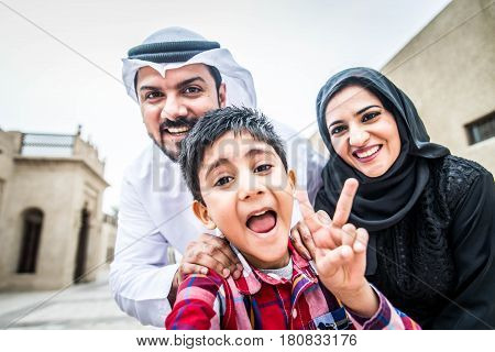 Arabic family playing with child and taking selfie