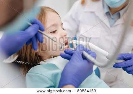 Ate too much candies. Docile admirable pretty child sitting a dentist chair and waiting patiently while the doctors doing their job