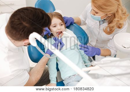 No caries is allowed. Admirable patient little girls sitting at dentists chair while he conducting a procedure and his colleague calming her down