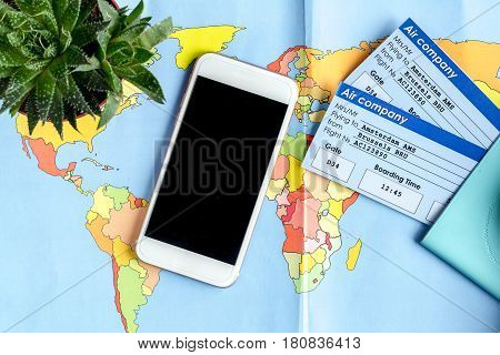 tourist lifestyle with mobile phone and flight tickets on map background top view