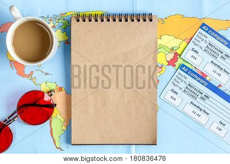 journey planning with tourist outfit and flight tickets, map and notebook on wooden table background top view mock-up