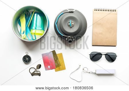 Preparation for traveling with loudspeaker, power bank and sunglasses on white desk background top view