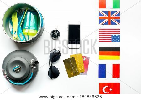 Traveler's accessories, mobile and credit cards in vacation concept on white table background top view