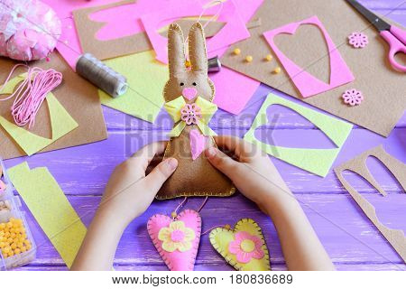 Small child holds a felt Easter bunny in his hands. Child made a felt cute bunny with hearts for Easter. Tools and materials for art creativity on a wooden table. Simple spring crafts project for kids