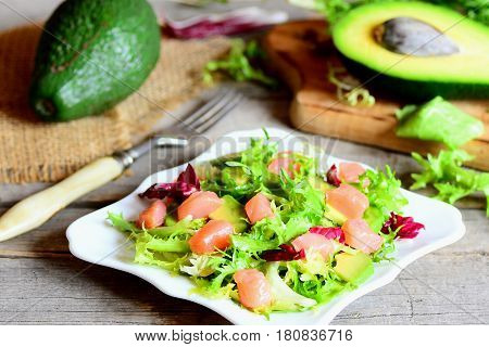 Salmon, avocado and lettuce salad. Homemade salad with slices of smoked salmon, fresh avocado and lettuce leaves mix on a plate. Avocado, fork on a wooden table. Closeup