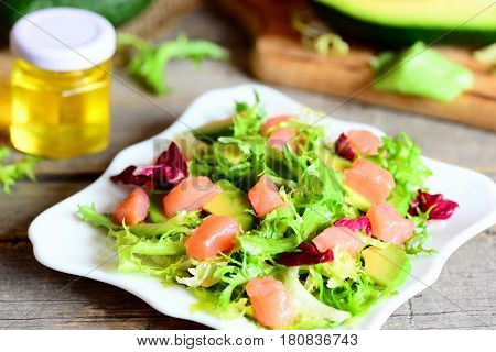Salmon, avocado and lettuce mix salad. Home salad with slices of smoked salmon, fresh avocado and lettuce leaves mix on a plate. Delicious and healthy appetizer. Closeup