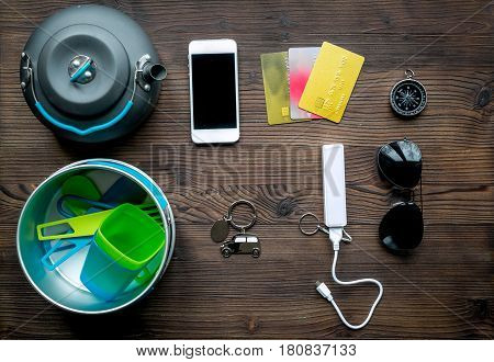 Outfit for trip with mobile and sunglasses on wooden table background top view