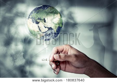 Hand of people holding the tobacco with smoke Burning the earth. World No Tobacco Day Concept and For Centers for Disease Control (CDC). Protecting people. Elements of this image furnished by NASA.