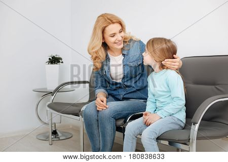 It will be fine. Beautiful supportive young mother looking at her child and making sure she not being very nervous before the visit to a doctor