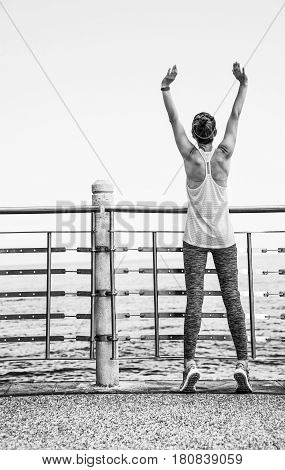 Relaxed Young Woman In Fitness Outfit Rejoicing At Embankment