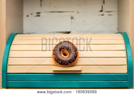 Colorful wooden breadbox decorated with donut in rustic style