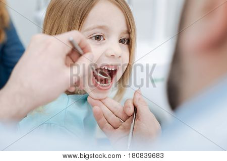 Almost smiling. Emotional orderly admirable girl behaving like a nice child and demonstrating her teeth for the doctor