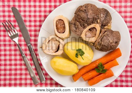 High angle view of a pot au feu a french beef stew on a white plate and checkered tablecloth