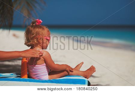 mother applying sunblock cream on daughter shoulder, sun protection