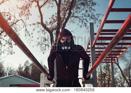 Young sporty man in high altitude mask working outdoors in winter background. Male adult exercising on parallel bars.