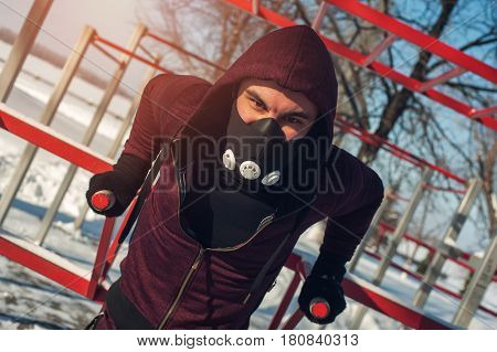 Fitness workout outdoors. Male muscular man wearing training mask doing exercises on parallel bars in winter.