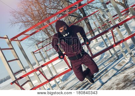 Winter fitness. Young male adult in high altitude training mask working out.