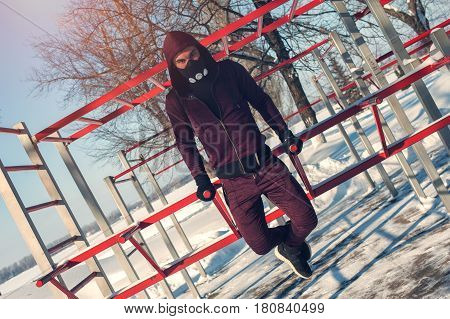 Young athletic adult doing triceps dips on parallel bars. Sporty man in training mask doing fitness workout in winter background.