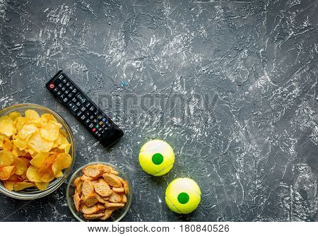 TV remote control and snacks on dark desk background top view space for text