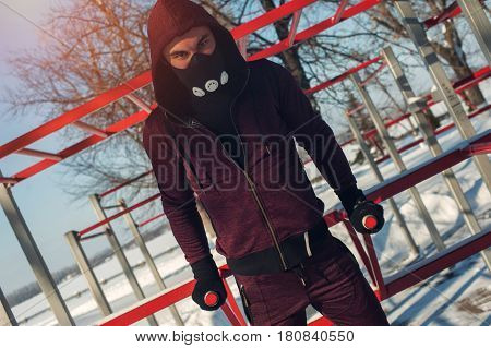 Young man in training mask exercising on parallel bars outdoors. Winter fitness.
