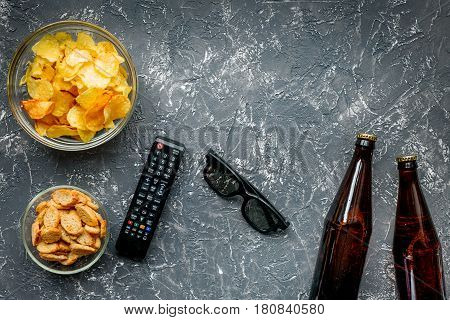 watching movies set with chips, beer and remote control on dark background top view mock up
