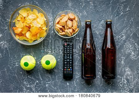 snacks for watching sport match with balls and beer on dark desk background top view