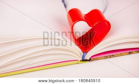 Red heart over diary book on white table. Side short, book slighly turned to right side