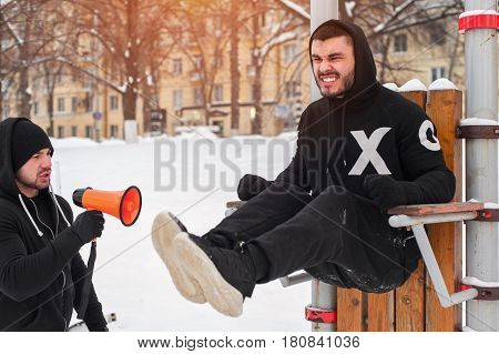 Fitness coach with loudspeaker and sporty man doing abdominal exercises outdoors. Trainer motivating via megaphone.