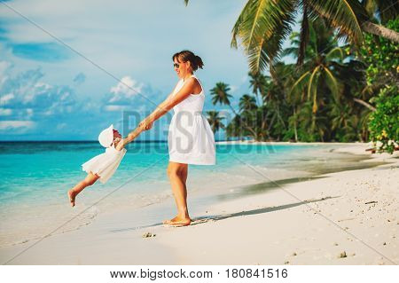 mother and little daugher playing on tropical beach